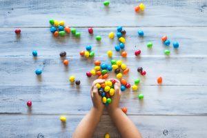 子供の手がいっぱいお菓子をもっている